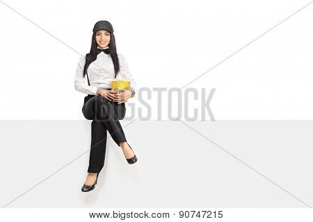 Young woman in an artistic outfit holding a box of popcorn and sitting on a blank panel isolated on white background