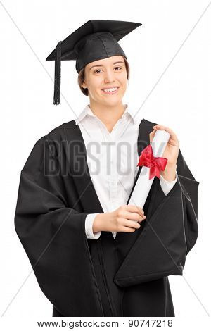 Vertical shot of a young woman in graduation gown posing with a diploma and looking at the camera isolated on white background