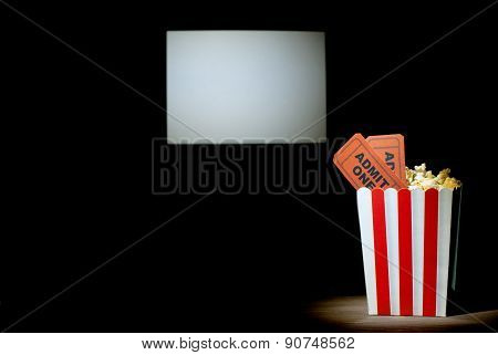 A box of popcorn with two tickets on white background screen cinema