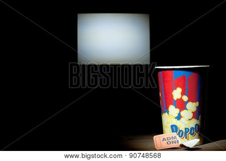 Empty box of popcorn next used torn ticket on the background screen cinema