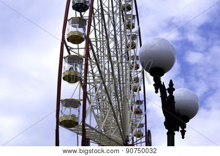 Ferris Wheel On The Blue Sky With Clouds Background