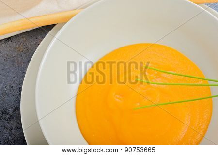 Orange pumpkin cream soup and green onion