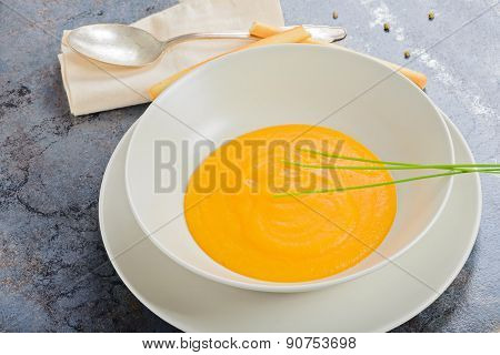 Pumpkin creamy soup with spoon and napkin