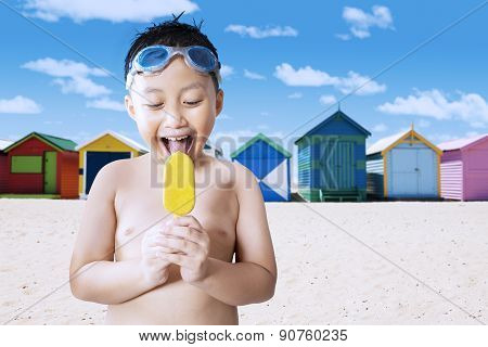 Happy Little Boy Licking Ice Cream At Shore
