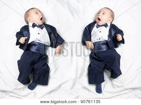 Mirrored photo of cute baby boy wearing an elegant suit with bow tie