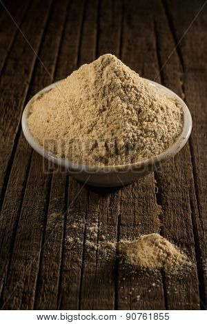 Asafoetida powder against wooden background