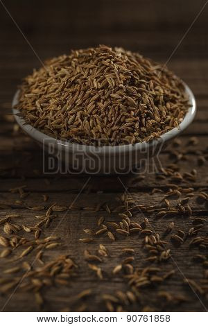 Cumin seeds against wooden background