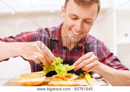 Man adding lettuce leaves  to his sandwich