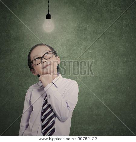 Smart Little Businessman Under Lit Bulb