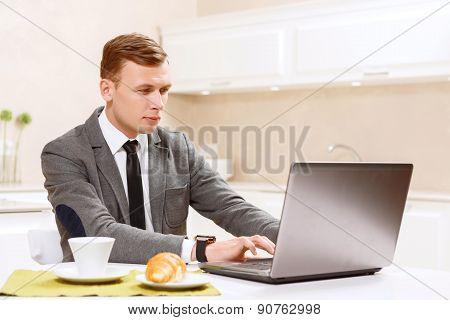 Man in suit working on computer kitchen