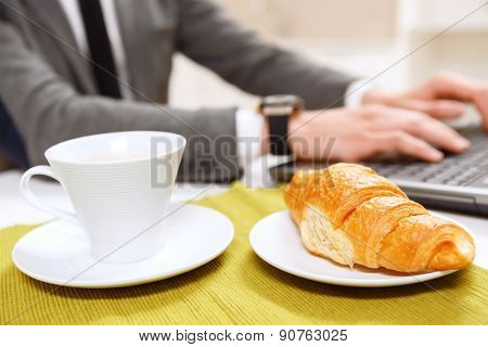 Close up of croissant and cup coffee.