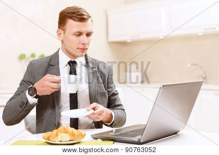 Businessman drinking coffee and working on computer