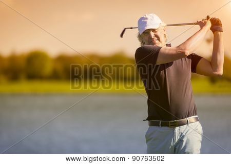 Male senior golf player swinging golf club with lake in background at sunset with sunflare.