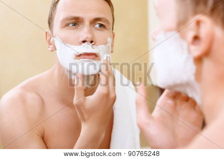 Topless man applying mean of shaving on face