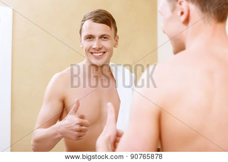 Smiling topless man with thumb-up in front mirror.