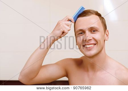 Topless man brushing his hair