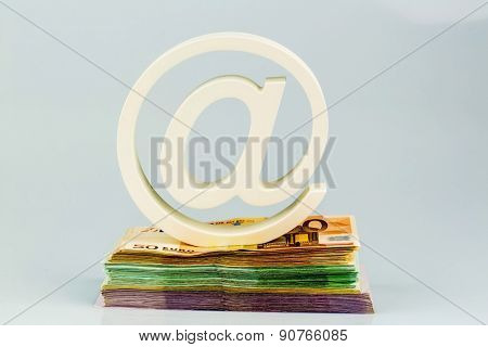 The at symbol, or commercial at, on a pile of banknotes.