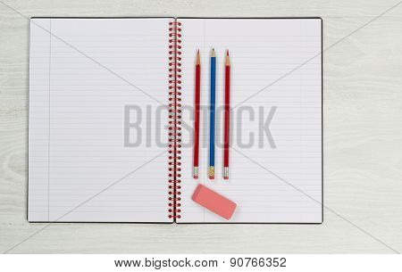Blank Notepad With Pencils And Eraser On Desktop
