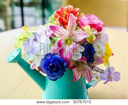 Artificial flowers in ceramic vase on the table.