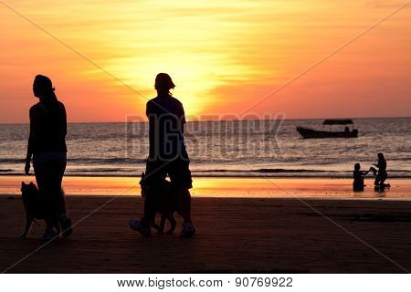 Unidentified couple walking with their dogs during a beautiful sunset in Manta beach