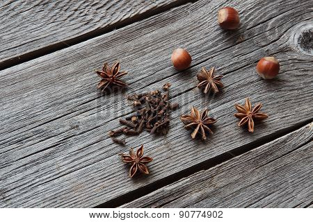 Wood Nut, Cinnamon Sticks, A Carnation And Anise Asterisks On A Wooden Background