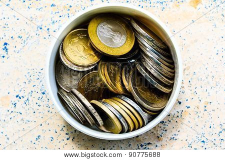 Collection of coins from various countries stored in a cup on a blurred background
