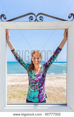 Happy woman in window in front of blue sea and beach