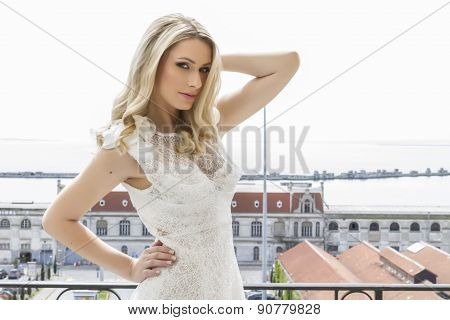 Beautiful Bride At The Balcony Of Luxury Hotel Room With Wedding Dress