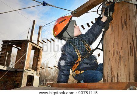 Little Boy Sits On Suspension Bridge And Adjusts Equipment
