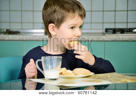 Little Boy Bites Cookies, Sitting At The Dinner Table.  Horizontal