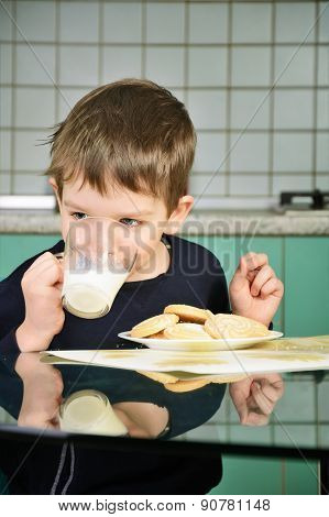 Cheerful Little Boy Drinking Milk, Sitting At The Dinner Table. Vertical