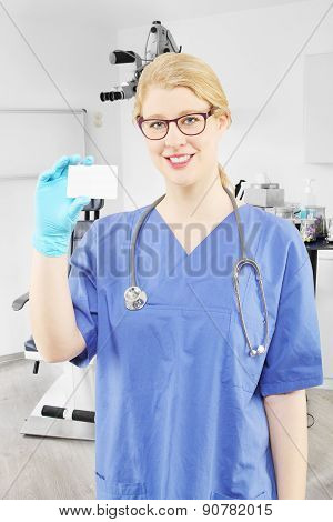 Blond female doctor in a doctor's office with a card