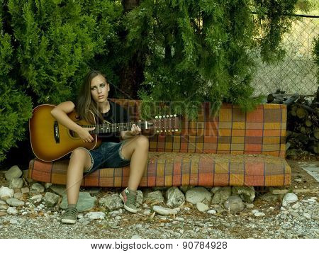 Portrait Of A Beautiful Girl Playing With A Guitar On A Sofa In The Forest