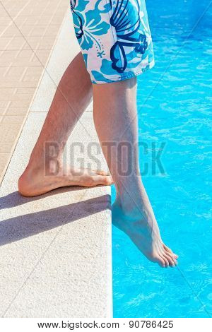 Legs with foot feeling water temperature in swimming pool