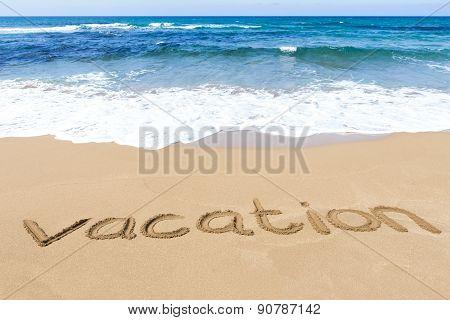 Word vacation written on sandy beach near sea