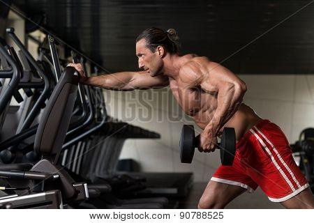 Bodybuilder Exercising Back With Dumbbell