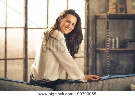 Elegant Woman Sitting On Back Of Sofa Smiling Over Shoulder