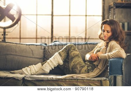 Woman Sitting On Sofa In Loft Relaxing