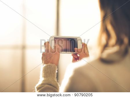 Closeup Of Woman Seen From Behind Holding Mobile Phone