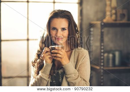 Head And Shoulder Shot Of Woman Holding Cup In Loft Apartment