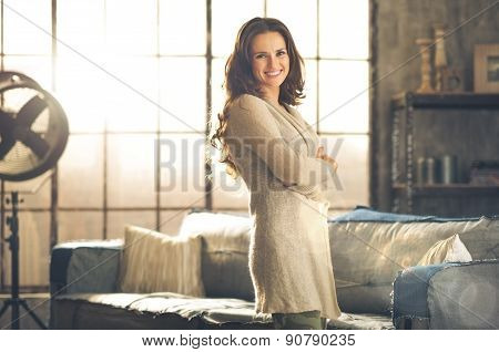 Casual Brunette With Arms Crossed Smiling In Loft Apartment