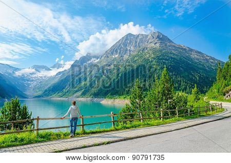 young woman stands by mountain lake , Austria
