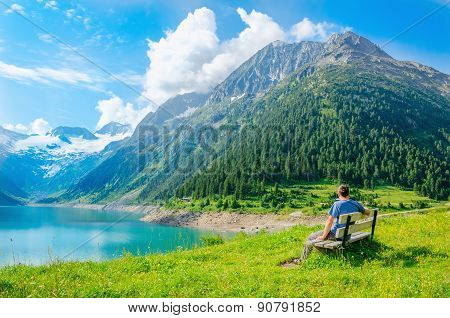 Young man sits on bench by mountain lake, Austria