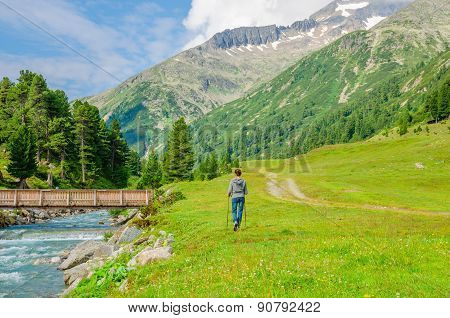 Young woman mountaineer walking by mountain stream