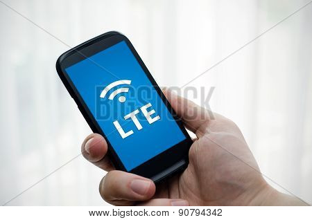 Hand Holding Mobile Phone With Lte Fast Internet Technology