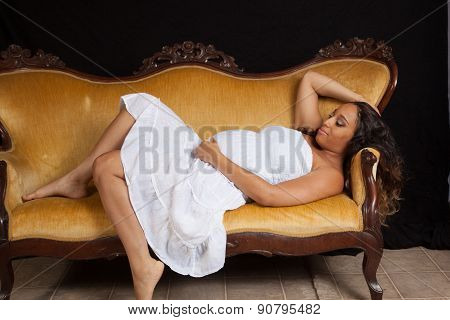 Pretty pregnant woman reclining on a couch