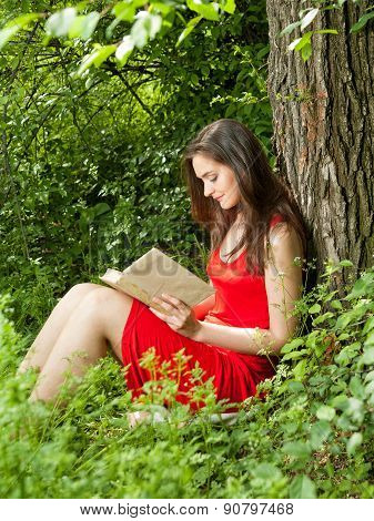 Gorgeous Brunette Woman Reading A Book In The Park