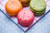 stock photo of mints  - Macarons put close together on blue table and white cloth with colorful and backlight - JPG