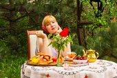 foto of curvaceous  - Beautiful Russian girl with a curvaceous rosy and happy sitting at a table with treats  - JPG