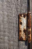 stock photo of wooden door  - Rusty door hinges on a shattered wooden door background - JPG